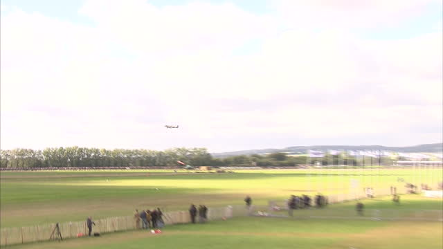 exterior shots of spitfire and hurricane planes taking part in a spectacular flypast at goodwood during the 75th anniversary commemoration event of... - 参加者点の映像素材/bロール