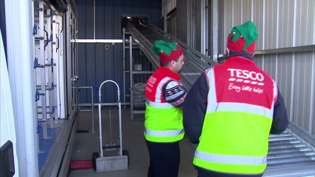exterior shots of staff wearing festive christmas hats loading boxes of groceries onto a van at a tesco online delivery centre tesco online grocery... - tesco点の映像素材/bロール