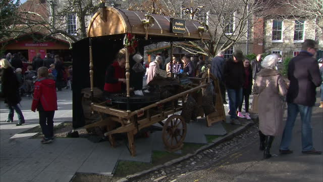 exterior shots of stallholders selling caramelised nuts toasted marshmallows and roast chestnuts at a christmas market in winchester>> on december 12... - 英国ハンプシャー点の映像素材/bロール