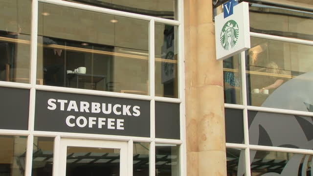exterior shots of starbucks coffee shop on march 30 2017 in london england - coffee cup stock videos & royalty-free footage