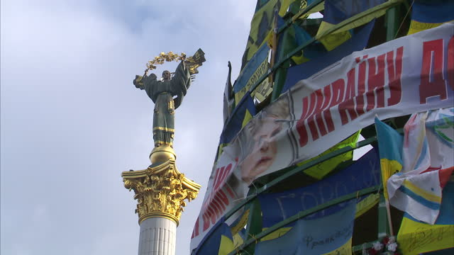 Exterior shots of statue of Archangel Mikhail in middle of Independence Square Kiev with opposition protest banners flags etc in foreground Archangel...