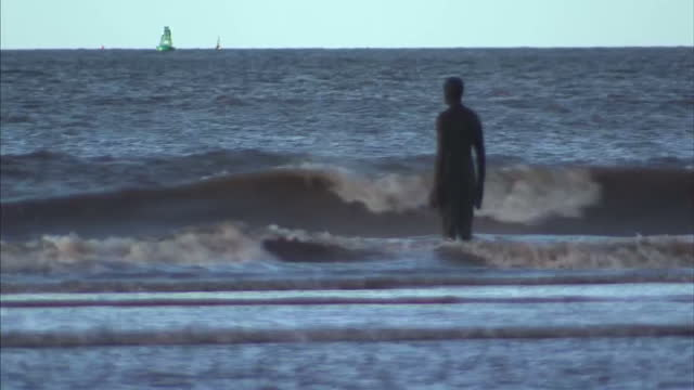Exterior shots of statues on Crosby beach from Another Place Artwork by Antony Gormley with statues in sand on beach and in the sea Antony Gormley's...