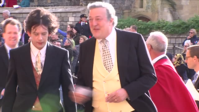 vídeos de stock e filmes b-roll de exterior shots of stephen fry and elliott spencer arriving at st george's chapel for the wedding of jack brooksbank and princess eugenie on 12... - stephen fry