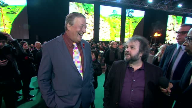Exterior shots of Stephen Fry hugging and speaking to director Peter Jackson on the green carpet at the premiere of 'The Hobbit The Battle of the...