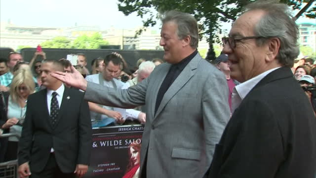 exterior shots of stephen fry on red carpet posing for photo op and signing autographs. on september 21, 2014 in london, england. - stephen fry stock videos & royalty-free footage