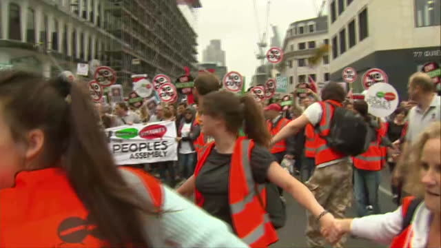 vídeos de stock, filmes e b-roll de exterior shots of stewards in orange vests linking hands in a circle and walking in front of crowds of protesters as they march through london... - vest