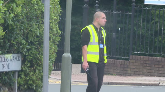 vídeos y material grabado en eventos de stock de exterior shots of street scenes around golders green as jewish people in traditional dress walk and a security guard stands outside a synagogue on 20... - golders green