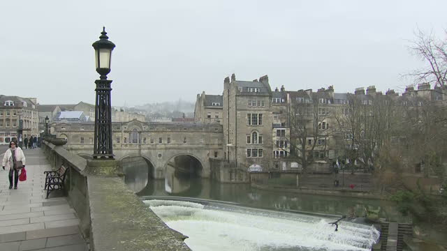 exterior shots of street scenes in bath including shoppers walking along a high street and tourists browsing outside a gift shop and views of a park... - bath stock videos & royalty-free footage