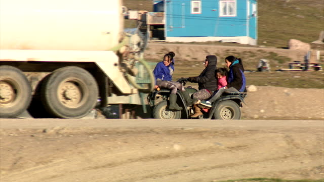 exterior shots of street scenes in pond inlet including shots of local people driving all terrain vehicles around town and signs written in english... - inuit stock videos & royalty-free footage