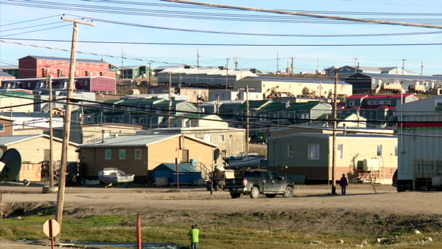 exterior shots of street scenes in pond inlet, including shots of people driving trucks and all terrain vehicles around town, and children looking on... - inuit bildbanksvideor och videomaterial från bakom kulisserna