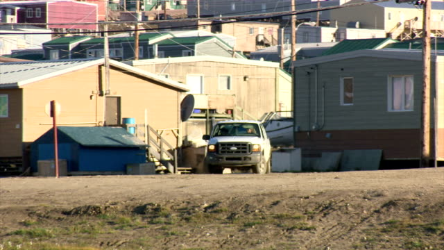exterior shots of street scenes in pond inlet including shots of people driving trucks and all terrain vehicles around town and a stream flowing... - inuit stock videos & royalty-free footage