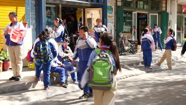 exterior shots of street scenes in urumqi, including police, a group of school pupils and street food vendors.>> on september 23, 2015 in urumqi,... - 新疆ウイグル自治区点の映像素材/bロール