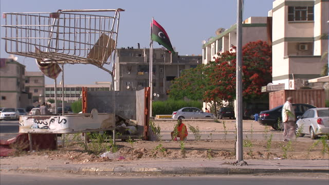 exterior shots of street scenes local people working on a construction site and flags of libya on june 10 2015 in tripoli libya - rifugiato video stock e b–roll