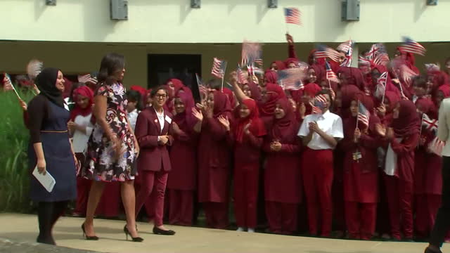 exterior shots of students cheering and waving flags as michelle obama, first lady of the united states walks into a courtyard during a visit to... - 2015 stock videos & royalty-free footage