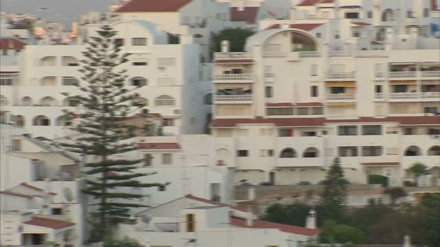exterior shots of sun setting over holiday villa rooftops in albufeira and other sprawling hotel apartment complexes near the seafront of the popular... - guia stock videos & royalty-free footage