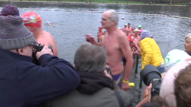 exterior shots of swimmers getting out of the serpentine lake in london's hyde park and being handled mulled wine after the annual peter pan cup on... - the serpentine london stock videos & royalty-free footage