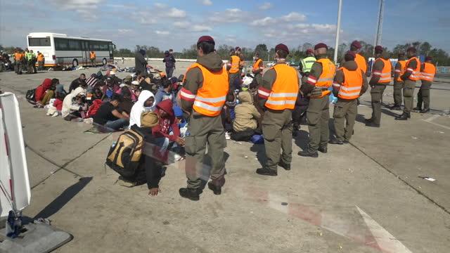 exterior shots of syrian migrants including men women children arriving at a austrian processing centre and queuing for checks on september 20 2015... - immigrant bildbanksvideor och videomaterial från bakom kulisserna