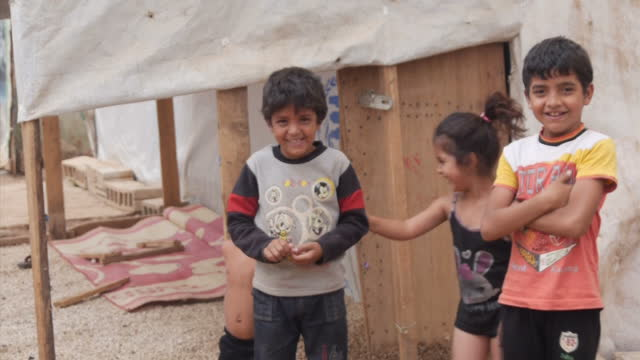 Exterior shots of Syrian refugee families including young children in a Lebanese refugee camp walking amid tents provided by the UNHCR on September 9...