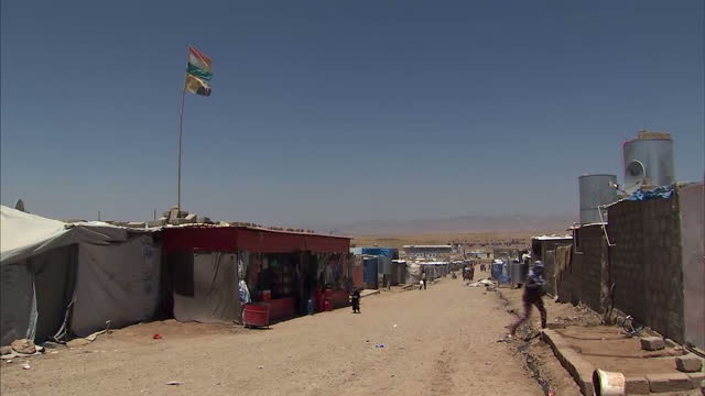 exterior shots of syrian women & children at the domiz refugee camp, with kurdish flags erected across the camp. syrian refugees at domiz refugee... - クルド人点の映像素材/bロール