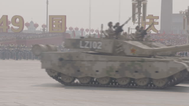 exterior shots of tanks, troop transports and trucks carrying military gyrocopters through tiananmen square in a parade celebrating the 70th... - parade stock videos & royalty-free footage