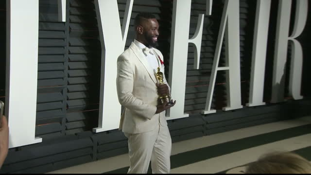 exterior shots of tarell alvin mccraney posing with his oscar for best adapted screenplay and being hugged by moonlight producer adele romanski on... - oscar party stock-videos und b-roll-filmmaterial
