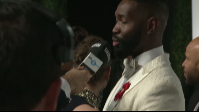 vídeos de stock e filmes b-roll de exterior shots of tarell alvin mccraney winner of the best adapted screenplay oscar speaking to reporters at the vanity fair oscars party - festa do óscar