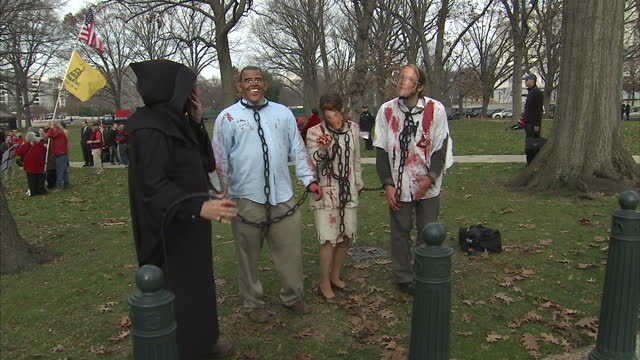 exterior shots of tea party activists in fancy dress in a protest against obamacare dressed as barack obama the grim reaper et al on december 15 2009... - tea party stock videos and b-roll footage