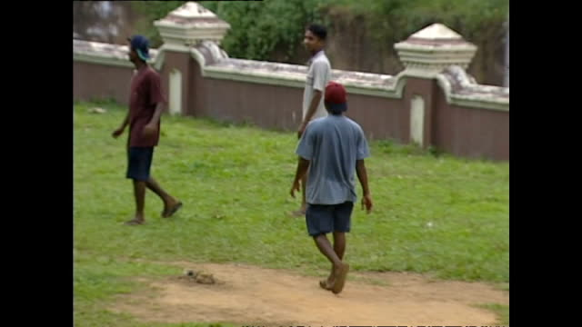 exterior shots of teenage boys playing cricket and football near an orphanage in galle please note it is not clear if these children have been... - waisenhaus stock-videos und b-roll-filmmaterial