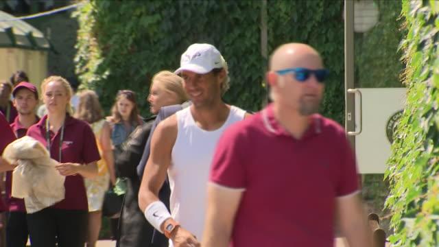Exterior shots of Tennis player Rafael Nadal at Wimbledon as he walks towards camera before practising at Wimbledon and ties his show laces before...