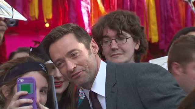 stockvideo's en b-roll-footage met exterior shots of the actor hugh jackman signing autographs and posing for photos with fans at the premiere of pan- n.b. reporter is speaking on... - signeren