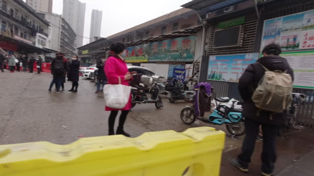 exterior shots of the area around huanan seafood market with people wearing masks on 24 january 2020 in wuhan china - wuhan stock-videos und b-roll-filmmaterial