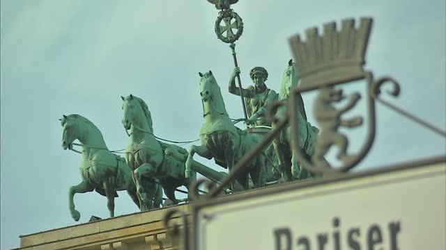 vídeos y material grabado en eventos de stock de exterior shots of the brandenburg gate including shots of the sign for pariser platz in the foreground and showing details of the bronze quadriga and... - entabladura