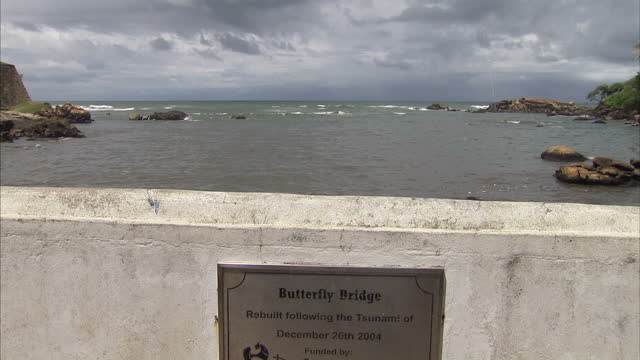 exterior shots of the butterfly bridge, rebuilt after the 2004 tsunami and a memorial plaque for victims on september 2, 2014 in galle, sri lanka. - 飾り板点の映像素材/bロール