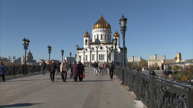 exterior shots of the cathedral of christ the saviour with pedestrians walking across the footbridge in the foreground and showing its gilded domes... - gilded stock videos & royalty-free footage