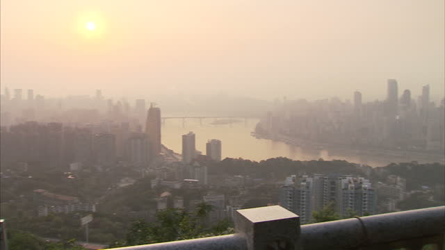 exterior shots of the chongqing city skyline, with buildings shrouded in fog or smog as evening approaches. wide shots of chongqing city skyline. on... - smog stock-videos und b-roll-filmmaterial