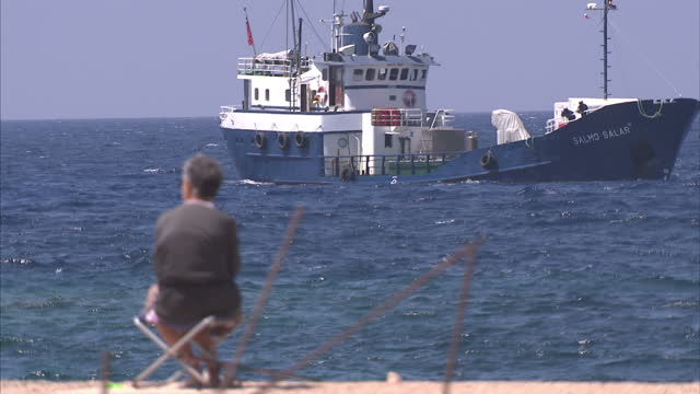 exterior shots of the coastline holidaymakers sunbathing on the beach and italian coastguard ships in the harbour on june 26 2015 in lampedusa italy - human trafficking stock videos & royalty-free footage