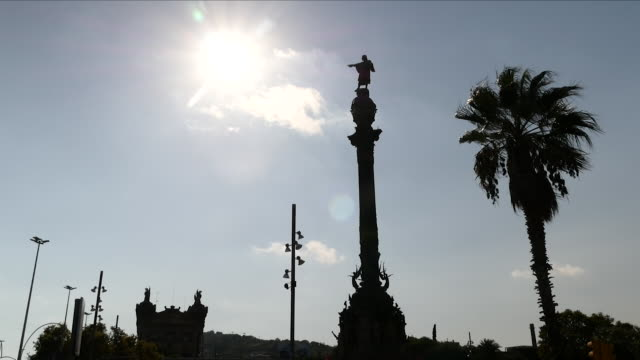 vídeos y material grabado en eventos de stock de exterior shots of the columbus monument with the sun behind it and a palm tree, on 11 october 2017 in barcelona, spain - puerto de barcelona
