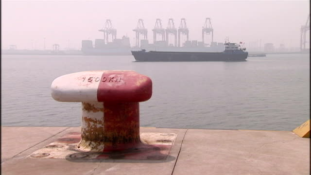 exterior shots of the container port with a container ship passing and another docked with cargo being loaded on board on august 12, 2009 in beijing,... - film container stock videos & royalty-free footage