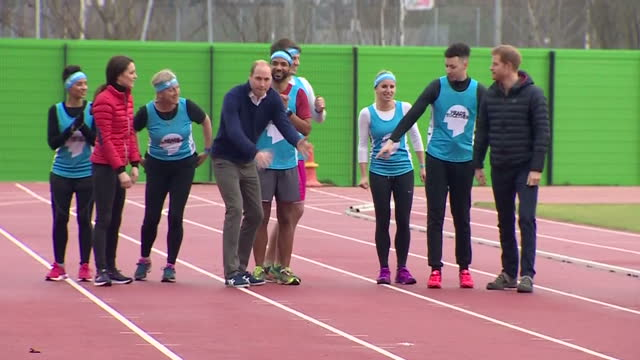 exterior shots of the duke and duchess of cambridge and prince harry taking part in a relay race during a training day for team heads together,... - ウィリアム王子点の映像素材/bロール
