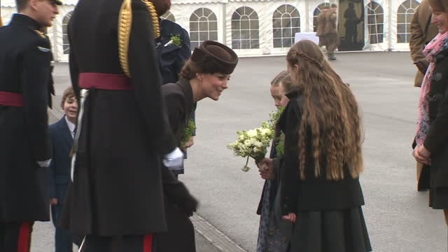 exterior shots of the duke and duchess of cambridge speaking to three young girls, who present the duchess of cambridge with a bouquet of flowers... - aldershot stock videos & royalty-free footage