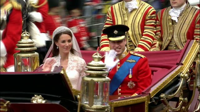 exterior shots of the duke & duchess of cambridge travelling in the 1902 state landau from westminster abbey to buckingham palace, waving at crowds... - 四輪馬車点の映像素材/bロール