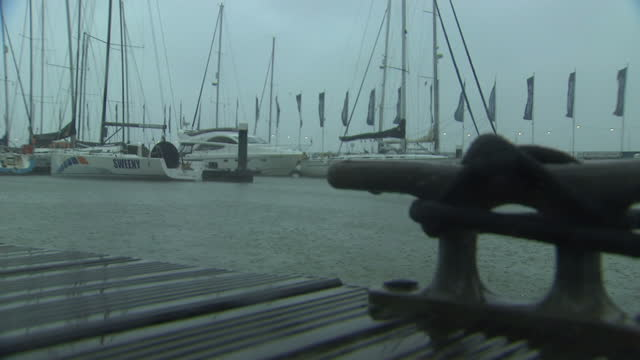 exterior shots of the empty promenade at a marina, with moored yachts rocking during rain and high winds.>> on august 10, 2014 in various cities,... - dondolarsi video stock e b–roll