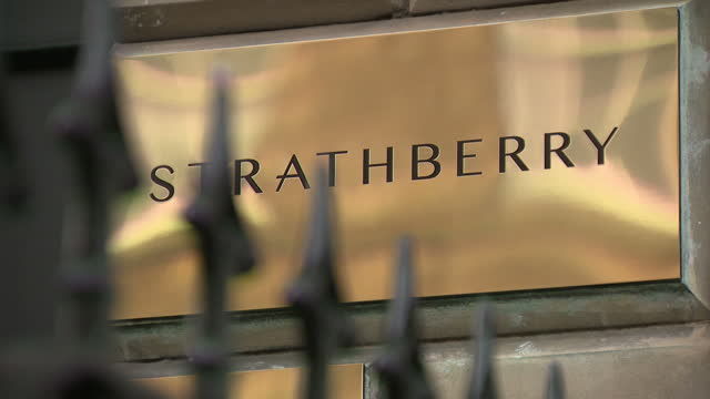 Exterior shots of the entrance to the Strathberry showroom in Edinburgh including shots of the shop's brass doorplate and Strathberry lettering in...