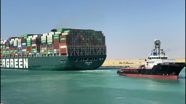 vídeos de stock e filmes b-roll de exterior shots of the ever given container ship, owned by evergreen marine, being pulled by tug boats after being stranded and blocking the suez... - evergreen