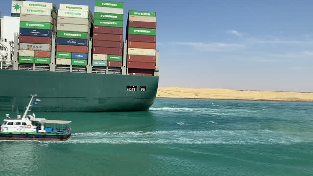 exterior shots of the ever given container ship, owned by evergreen marine, being pulled by tug boats after being stranded and blocking the suez... - evergreen stock videos & royalty-free footage