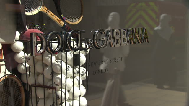 exterior shots of the fenwick and dolce and gabbana fashion boutiques on new bond street, with a display of vintage tennis kit on display in the... - dolce & gabbana stock videos & royalty-free footage