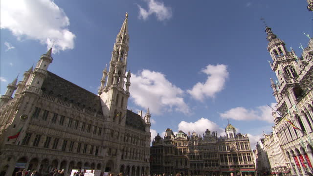 exterior shots of the grand place in brussels with tourists walking around the historic town hall with its belfry tower and gilt statue of the... - 天使ミカエル点の映像素材/bロール