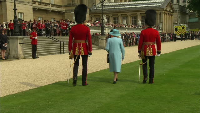 exterior shots of the grenadier guards walking back towards guard line in buckingham palace gardens queen turns walks back towards the steps up to... - 近衛兵点の映像素材/bロール
