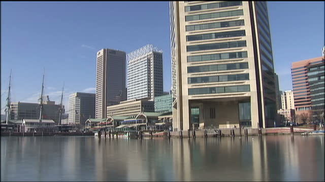 exterior shots of the inner harbor area of baltimore with ice on the bay and american flags flying near historic ships including the submarine uss... - hafen von baltimore stock-videos und b-roll-filmmaterial