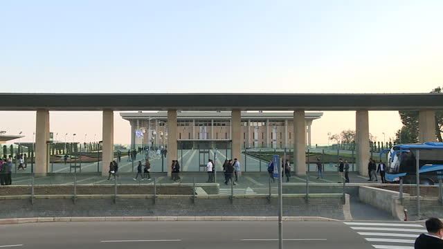 Exterior shots of the Knesset building with row of Israeli flags flying and people coming and going on February 06 2017 in Jerusalem Israel